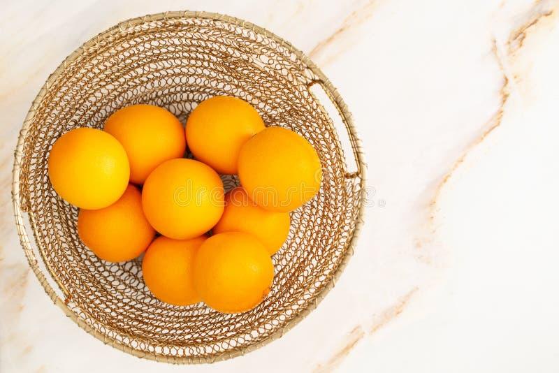 Opinión superior varias naranjas en una cesta de oro sobre un fondo de mármol imagenes de archivo