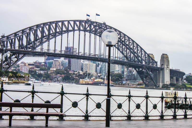 Opinión Sydney Harbour Bridge del Quay circular en una mañana mojada, con la ciudad en la distancia y un viaje en transbordador e foto de archivo libre de regalías