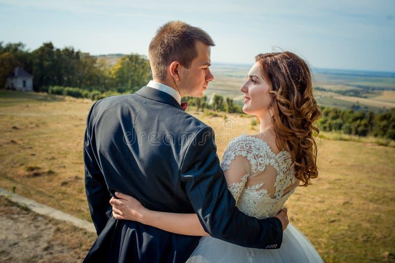 Opinión trasera del primer los recienes casados sonrientes encantadores que abrazan y que miran uno al fondo del fotos de archivo libres de regalías