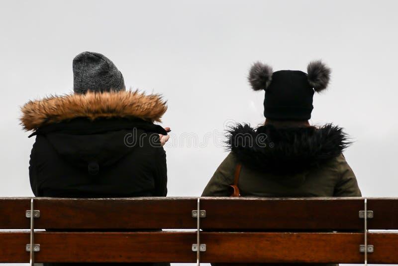 Opinión trasera dos muchachas con los sombreros del invierno que se sientan junto en el banco de madera aislado en blanco fotografía de archivo libre de regalías