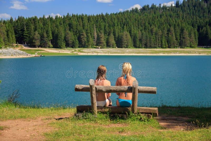 Opinión trasera dos muchachas que se sientan en un banco cerca de un lago de la montaña y de árboles de pino fotos de archivo libres de regalías
