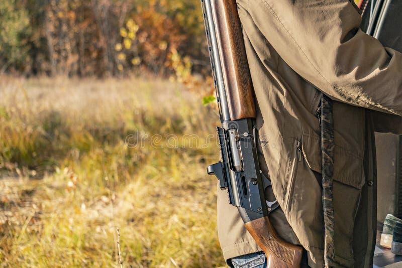 Opinión trasera el cazador llevar shotgu clásico del rifle en el bosque f foto de archivo
