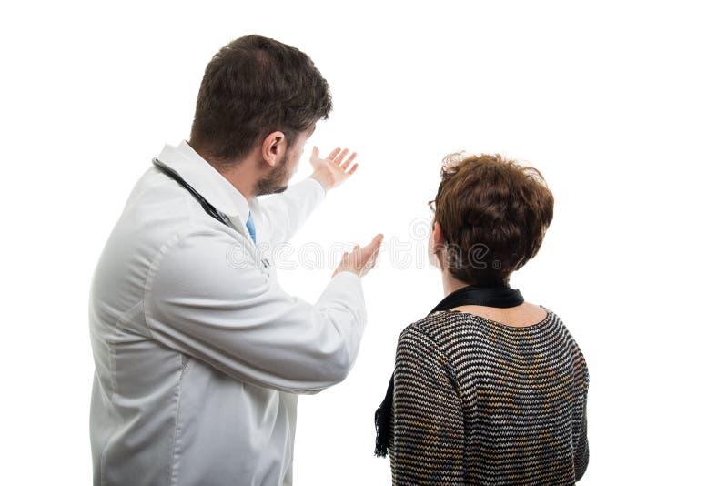 Opinión trasera el doctor de sexo masculino que muestra al paciente mayor femenino foto de archivo libre de regalías