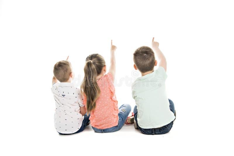 Opinión trasera el grupo del niño que se sienta en el piso que mira la pared imágenes de archivo libres de regalías