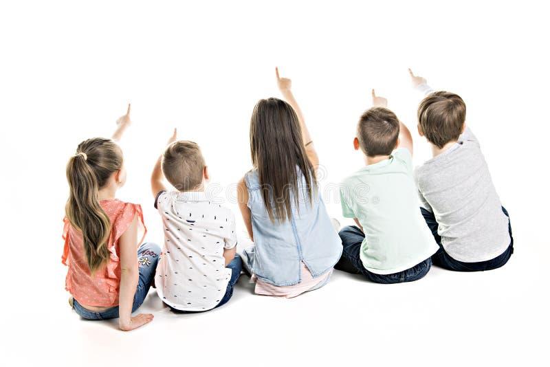 Opinión trasera el grupo del niño que se sienta en el piso que mira la pared imagen de archivo