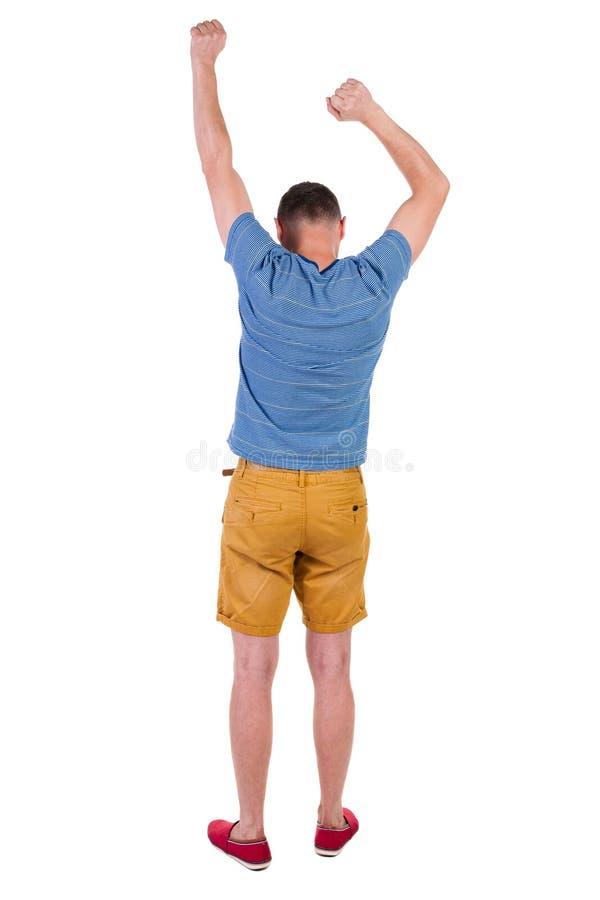 Opinión trasera el hombre alegre que celebra las manos de la victoria para arriba fotografía de archivo libre de regalías