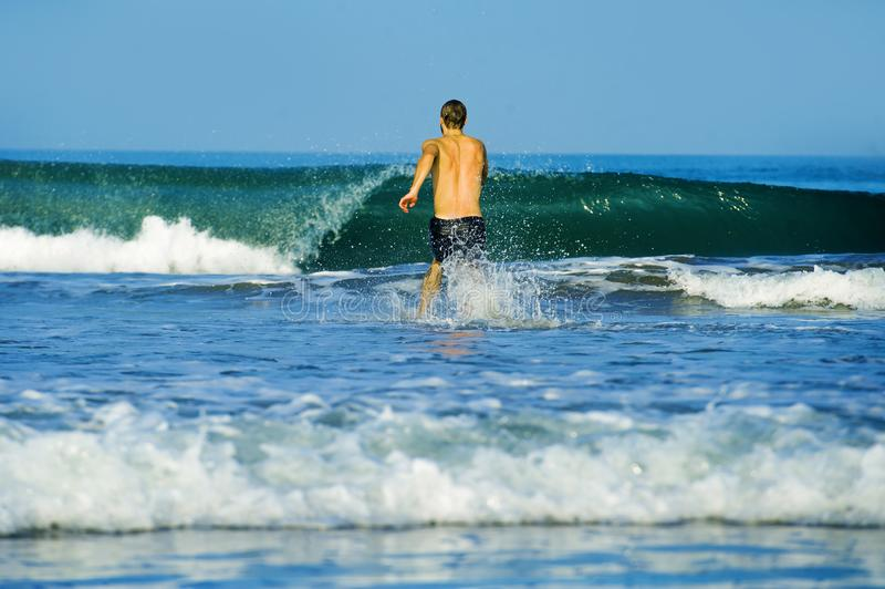 Opinión trasera el hombre atractivo y feliz joven en troncos de natación en el funcionamiento juguetón del paraíso de la play imágenes de archivo libres de regalías