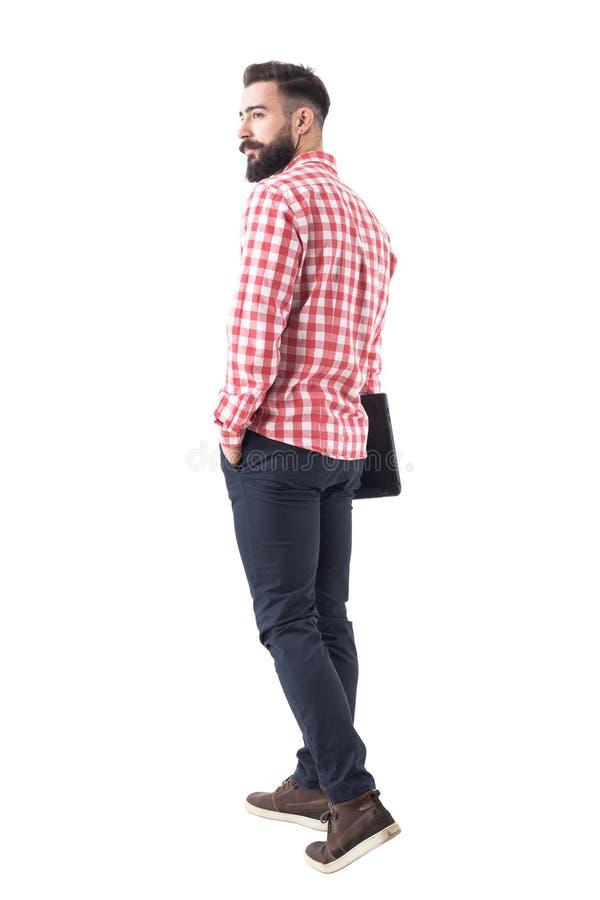Opinión trasera el hombre barbudo joven hermoso confiado que sostiene el ordenador portátil y que se va foto de archivo