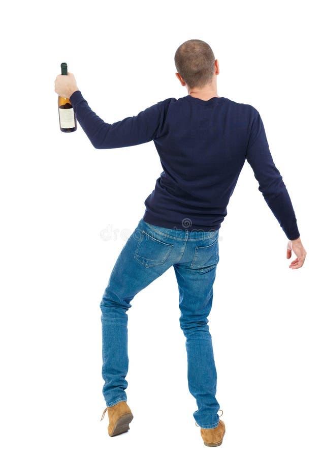 Opinión trasera el hombre borracho con el vino de la botella individuo joven de consumición fotos de archivo libres de regalías