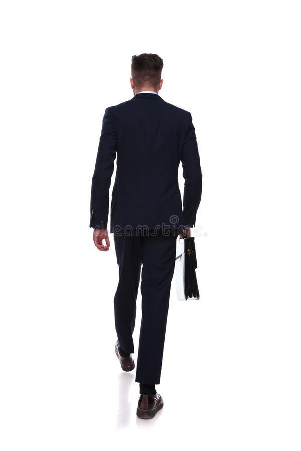 Opinión trasera el hombre de negocios de escalonamiento con la cartera a disposición fotos de archivo
