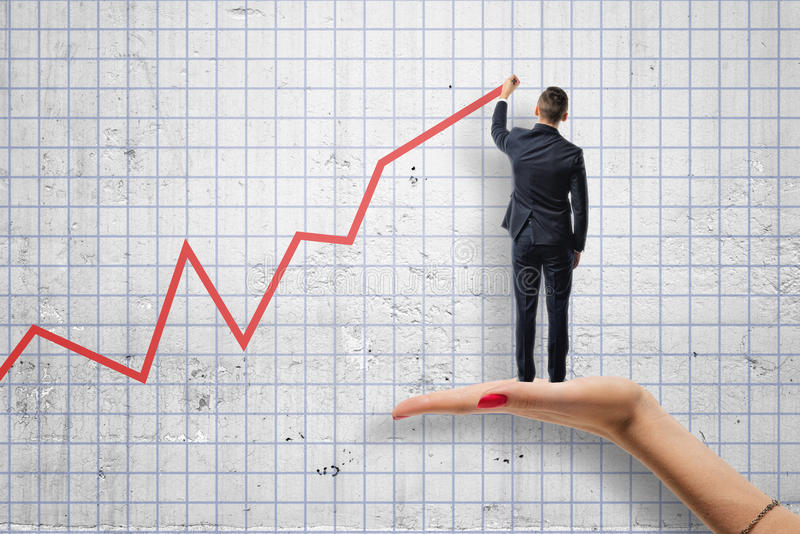Opinión trasera el hombre de negocios que dibuja un diagrama rojo que se coloca en el woman& x27; mano de s imagenes de archivo