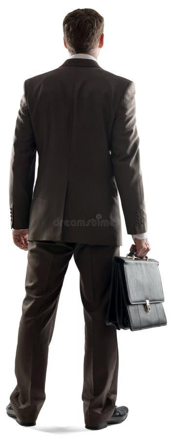 Opinión trasera el hombre de negocios que se coloca con la cartera foto de archivo