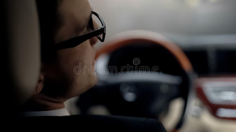 Opinión trasera el hombre de negocios triste que espera en el tráfico el atasco, tarde la reunión importante imagen de archivo