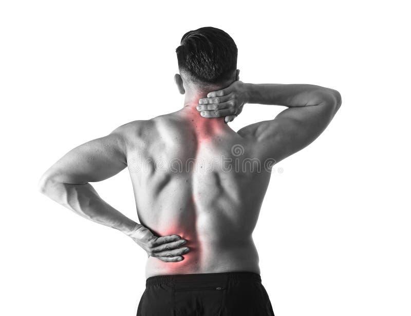 Opinión trasera el hombre joven con el cuerpo muscular que lleva a cabo su dolor espinal del cuello y del sufrimiento de espalda fotos de archivo