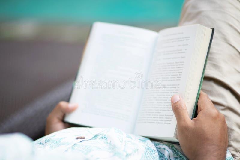 Opinión trasera el hombre joven en la ropa casual que abre y que lee un libro foto de archivo