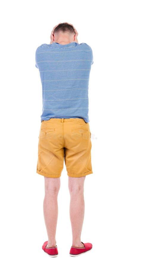 Opinión trasera el hombre joven enojado en pantalones cortos y camiseta foto de archivo