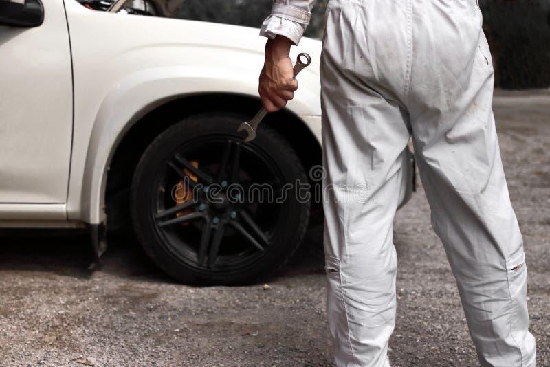 Opinión trasera el hombre joven profesional del mecánico en llave que se sostiene uniforme contra el coche en capilla abierta en  foto de archivo