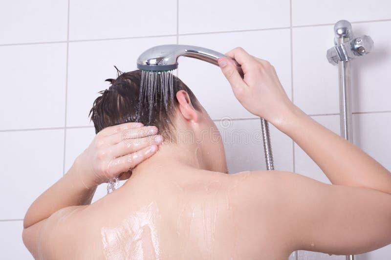 Opinión trasera el hombre joven que tiene una ducha fotografía de archivo