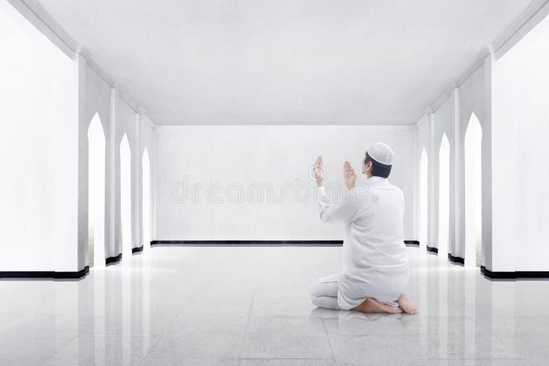 Opinión trasera el hombre musulmán asiático que se arrodilla y que ruega a dios fotografía de archivo