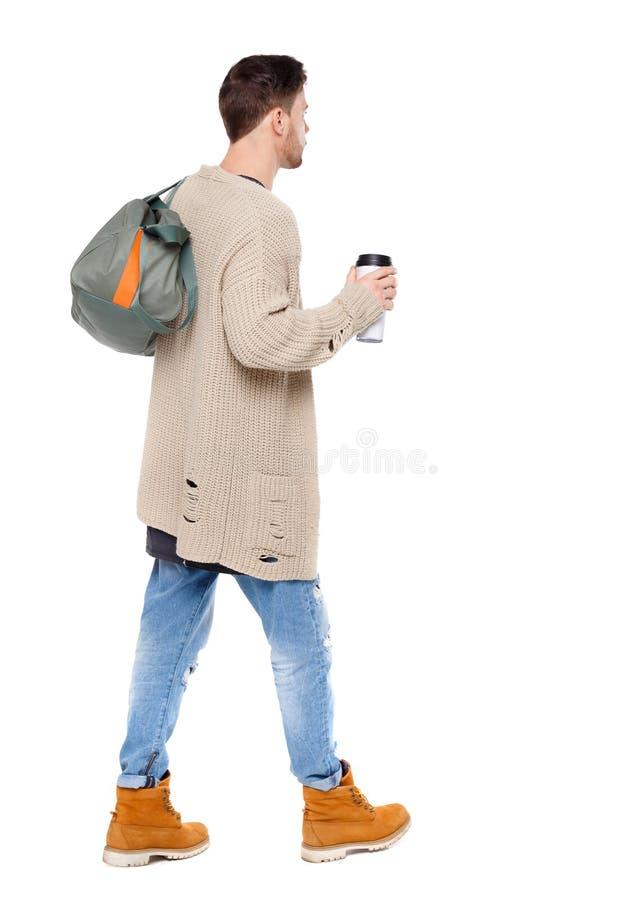 Opinión trasera el hombre que camina con la taza de café y el bolso verde imágenes de archivo libres de regalías