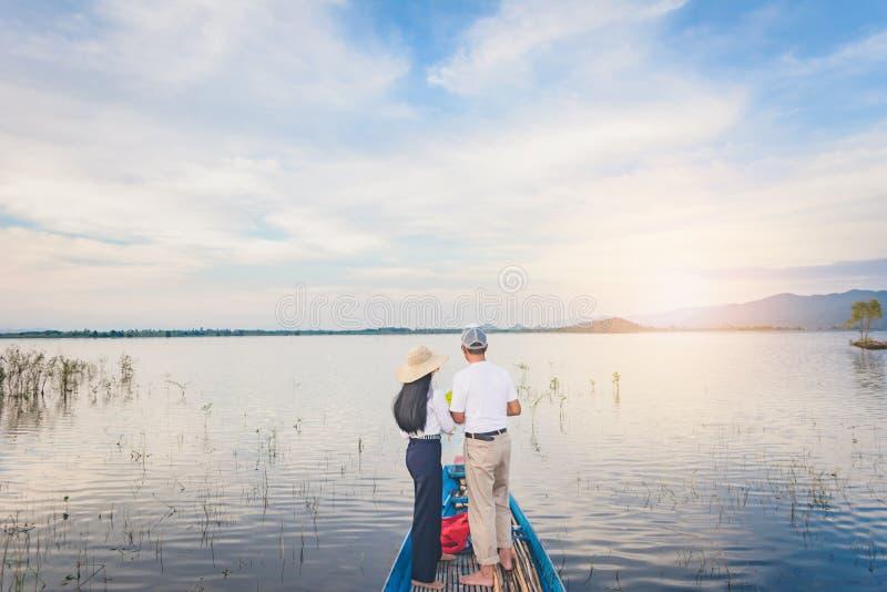 Opinión trasera el hombre y la mujer del viaje con el mapa que se coloca en el barco foto de archivo libre de regalías