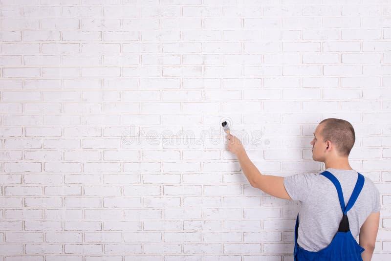 Opinión trasera el pintor del hombre en pared de ladrillo de la pintura del workwear con Br imagen de archivo libre de regalías