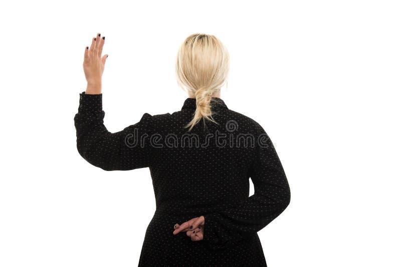 Opinión trasera el profesor de sexo femenino rubio que muestra gesto falso del juramento imagenes de archivo