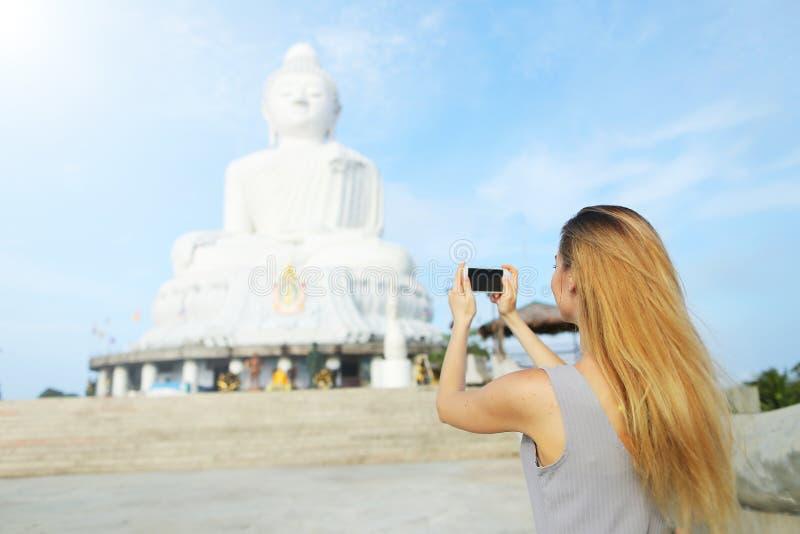 Opinión trasera la chica joven que toma la foto por la estatua de Buda del smartphone en Phuket, Tailandia foto de archivo libre de regalías