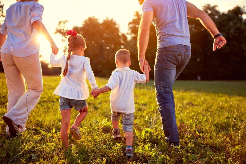 Opinión trasera la familia con los niños junto foto de archivo