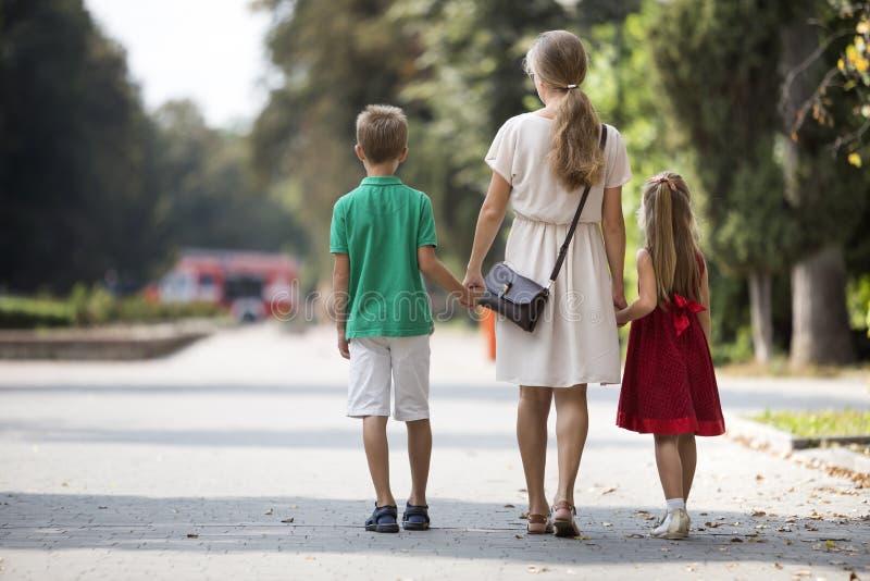 Opinión trasera la familia feliz, la mujer de pelo largo rubia joven que camina llevando a cabo las manos con dos niños, la peque imágenes de archivo libres de regalías