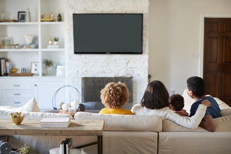 Opinión trasera la familia joven que se sienta en el sofá y la TV de observación junto en su sala de estar fotos de archivo