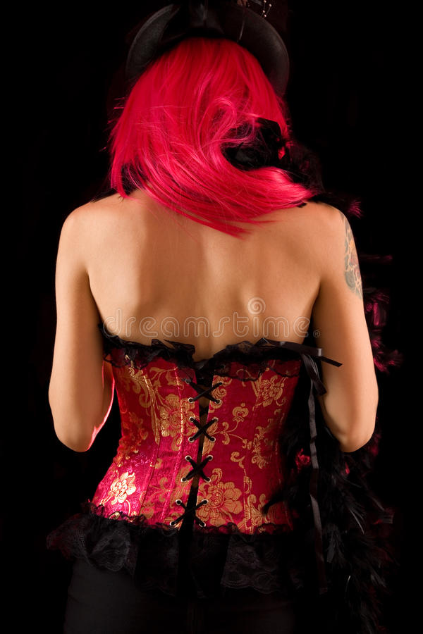 Opinión trasera la muchacha del cabaret en corsé y sombrero rosados foto de archivo