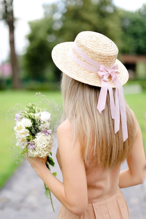 Opinión trasera la muchacha rubia joven en guardapolvos y sombrero del color de cuerpo con las flores imagen de archivo