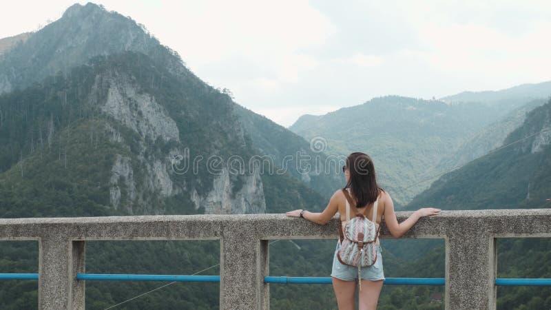 Opinión trasera la muchacha turística que se coloca en el puente Djurdjevic en Montenegro, forma de vida del viaje imagen de archivo