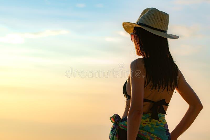 Opinión trasera la mujer asiática joven feliz en sombrero negro del traje de baño y de paja relajar y disfrutar de día de fiesta  fotos de archivo libres de regalías