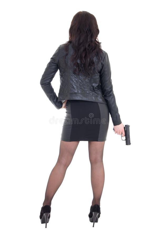 Opinión trasera la mujer atractiva en el arma que se sostiene negro aislado en blanco imagenes de archivo