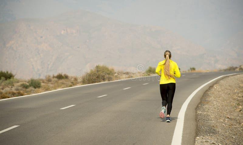Opinión trasera la mujer atractiva joven del deporte que corre en la carretera de asfalto de la montaña del desierto fotografía de archivo