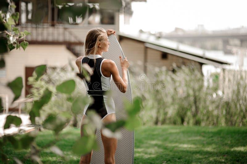 Opinión trasera la mujer atractiva rubia en soporte blanco y negro del traje de baño imagenes de archivo