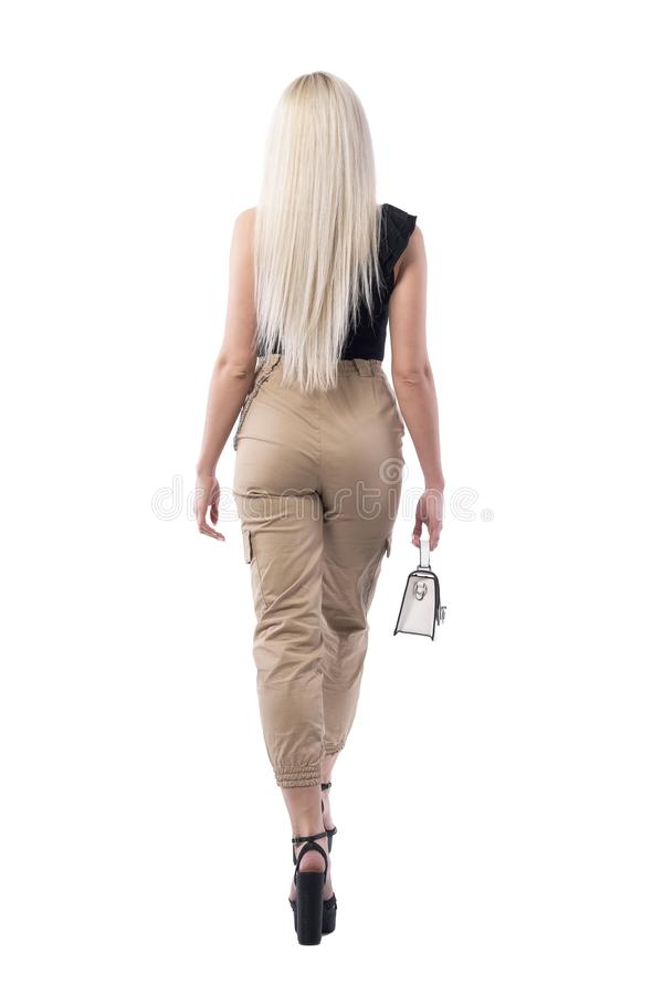 Opinión trasera la mujer atractiva rubia que se va con el pequeño bolso de moda imagen de archivo libre de regalías