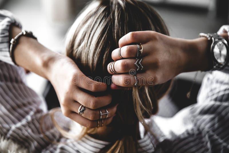 Opinión trasera la mujer bastante joven que ajusta su pelo, moda, estilo, anillos fotos de archivo libres de regalías