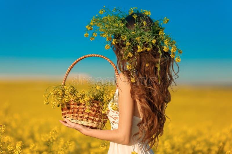 Opinión trasera la mujer con el pelo sano largo sobre fondo amarillo del paisaje del campo de la violación Muchacha morena de Att imagenes de archivo