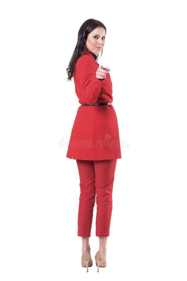 Opinión trasera la mujer de negocios joven en el traje rojo que da vuelta y que señala al finger en la cámara que le invita imagen de archivo libre de regalías