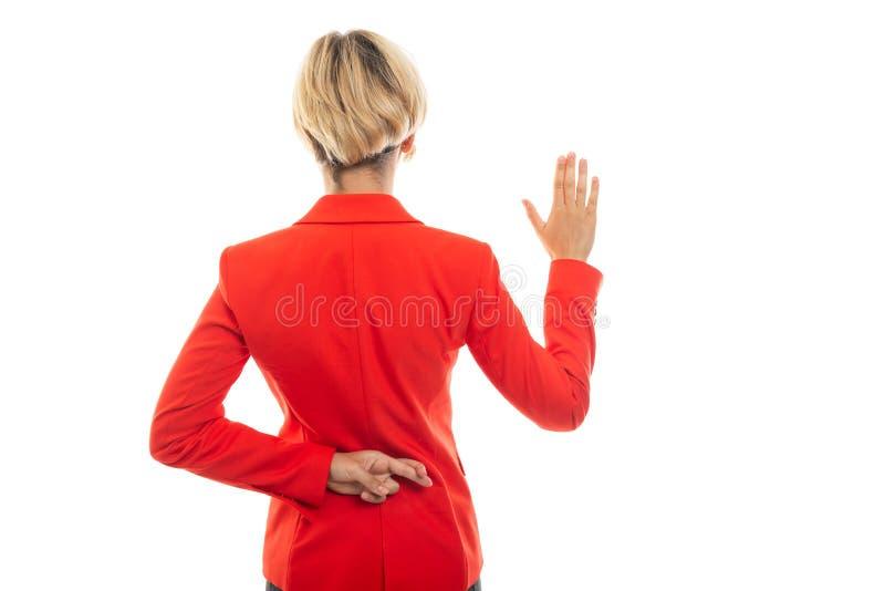 Opinión trasera la mujer de negocios que muestra gesto falso del juramento foto de archivo