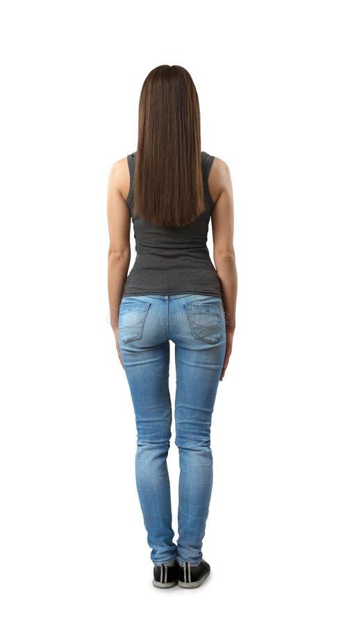 Opini?n trasera la mujer en blusa sin mangas gris y tejanos que se colocan con los brazos en los lados aislados en el fondo blanc foto de archivo libre de regalías