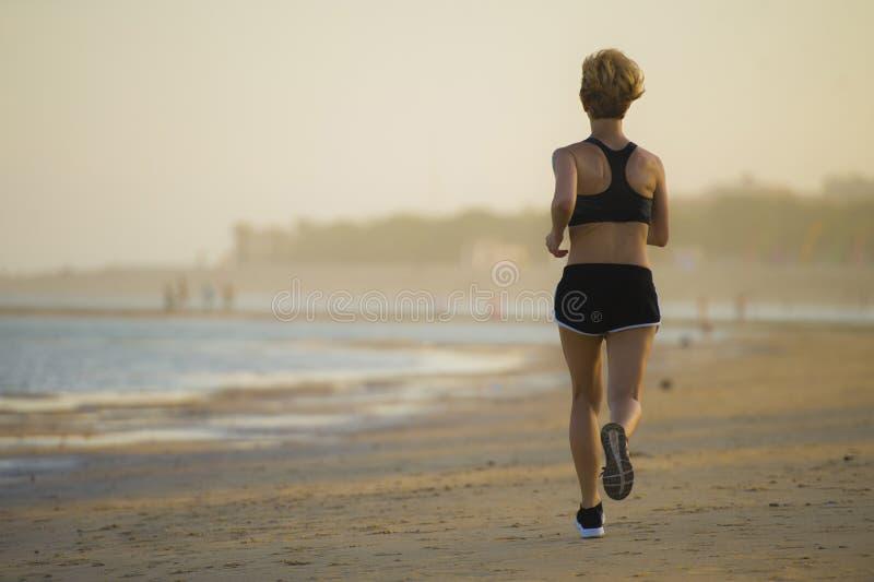 Opinión trasera la mujer feliz y atractiva joven del ajuste que corre en la playa en entrenamiento al aire libre que activa en el imagen de archivo