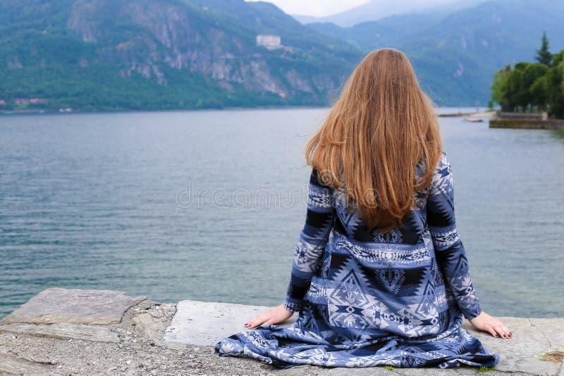 Opinión trasera la mujer joven con el pelo largo que se sienta cerca del lago Como, montaña en fondo fotos de archivo