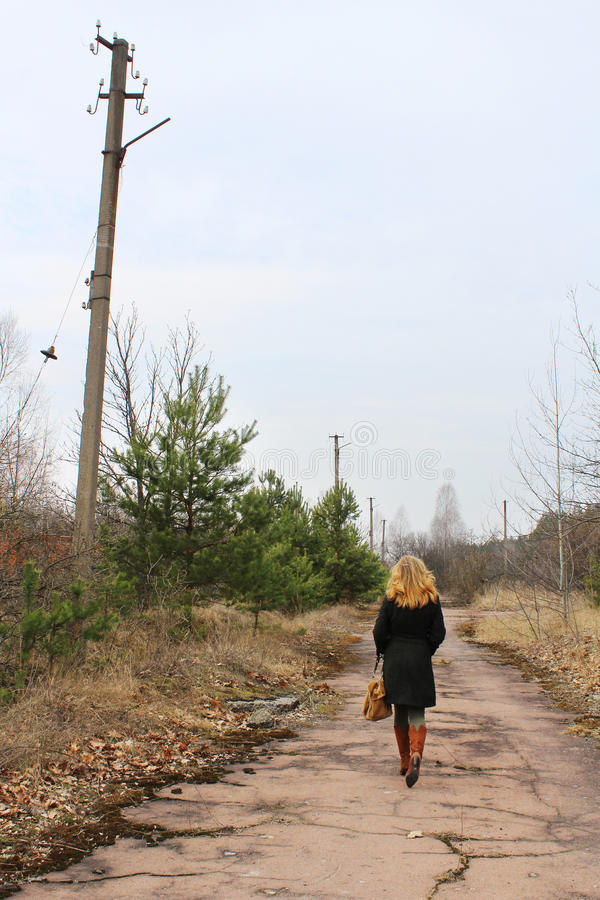 Opinión trasera la mujer joven de pelo largo en el camino abandonado imagen de archivo