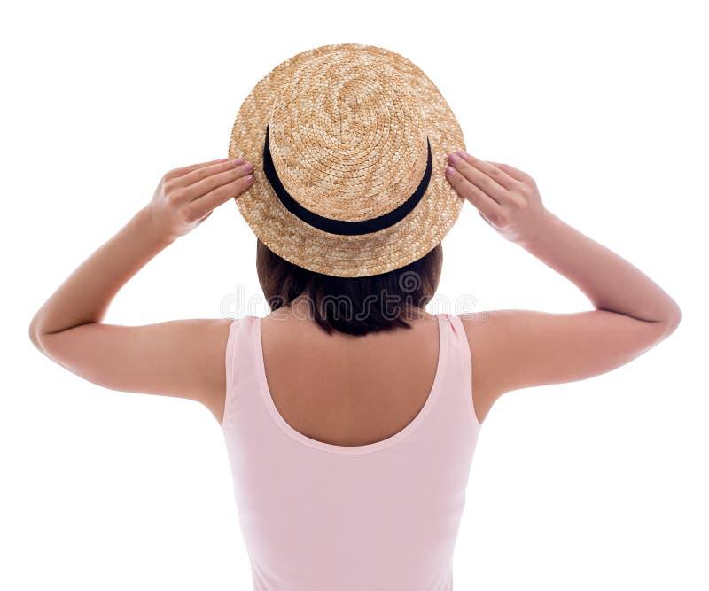 Opinión trasera la mujer joven en el sombrero rosado del traje de baño y de paja aislado en blanco foto de archivo