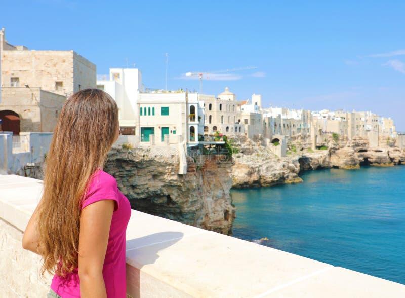 Opinión trasera la mujer joven hermosa en Polignano una ciudad de la yegua en el mar Mediterráneo, Italia imagen de archivo