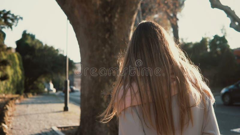 Opinión trasera la mujer joven que camina solamente en el centro de ciudad El ir femenino pensativo cerca del camino en día solea foto de archivo